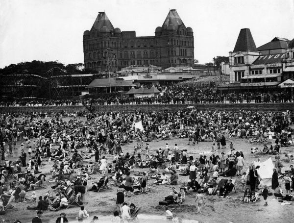 A crowded beach at New Brighton, Wallasey, Merseyside, with the Tower Ballroom and a children's fairground ride in the background
