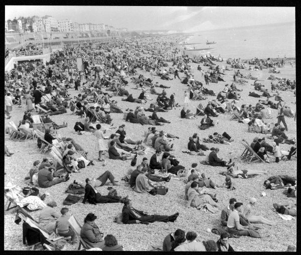 Brighton beach packed with people enjoying good weather on Easter bank holiday; some sit on deckchairs, others directly on the shingle