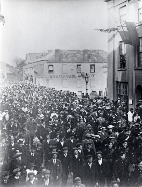 Crowds of people in the roadway at Victoria Place, Haverfordwest, Pembrokeshire, Dyfed, South Wales, probably during a circus procession. Lewis's Furnishing Warehouse can be seen in the background