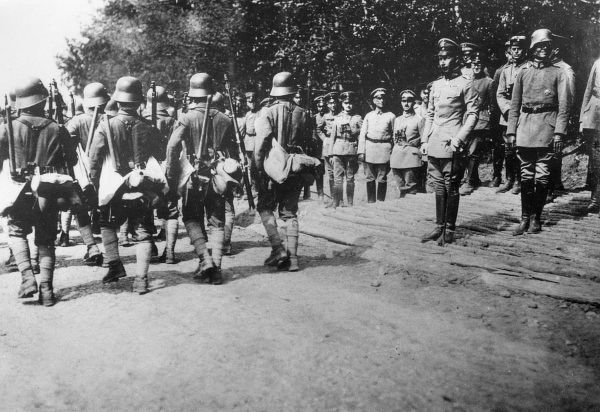Crown Prince Friedrich Wilhelm Victor August Ernst of Prussia (1882-1951). Seen here (right) at Charleville, France, watching a march past of soldiers. He was made commander of the 5th Army in August 1914, and continued in the role until November 1916