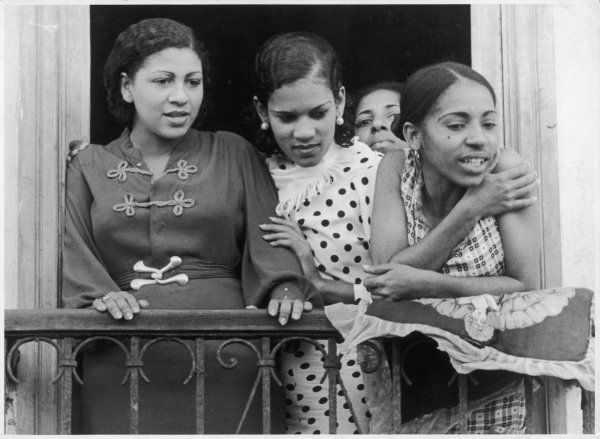 A young woman and a group of pretty teenage girls on a balcony in Havana, Cuba, West Indies