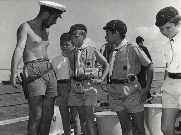 A young Naval Officer explains aspects of a Royal Navy ship to a group of Cub Scouts in Aden, Yemen