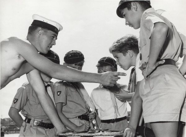 A young Naval Officer explains aspects of a Royal Navy ship to a group of Cub Scouts in Aden, Yemen. They lean over a piece of equipment and the officer points at one of the boys