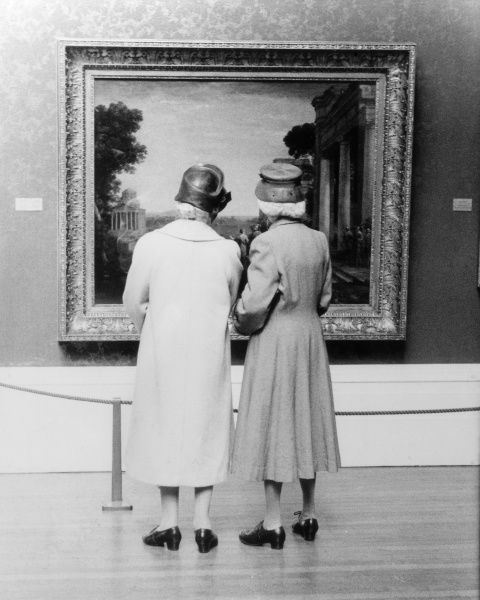 Two old dears admire an oil painting at an art gallery. Date: 1950s