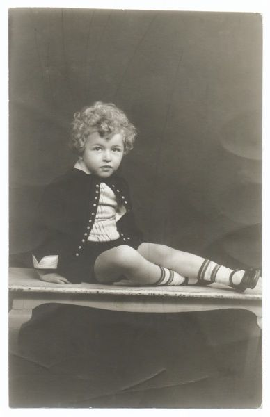 A curly haired little boy poses in the photographer's studio. He is wearing his best jacket and short trousers, and sitting on a table top