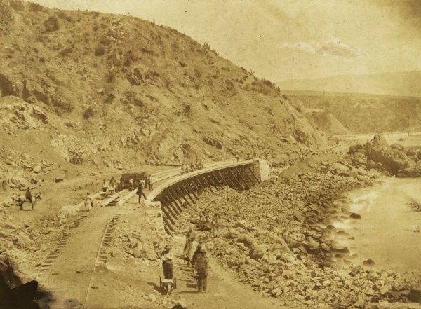 Curved section of railway track under construction by the sea, location unknown possibly Spain? Date