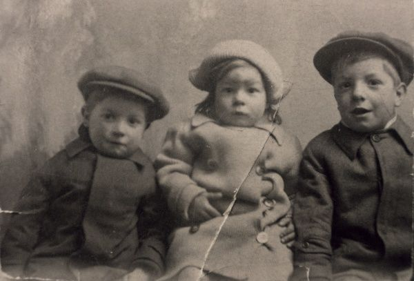 Three cute little children, two boys and a girl, dressed in their outdoor clothes. Date: circa 1915