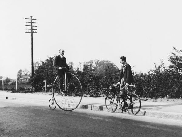 A meeting of cycles past and present occurs when a Penny Farthing encounters a modern bicycle outside Hatton, Middlesex