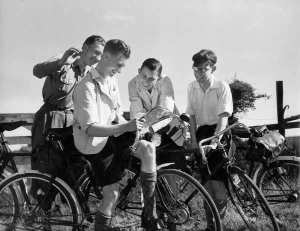 'Which way shall it be?' Four cycling club boys halt for a dicussion over a map. Date: 1930s