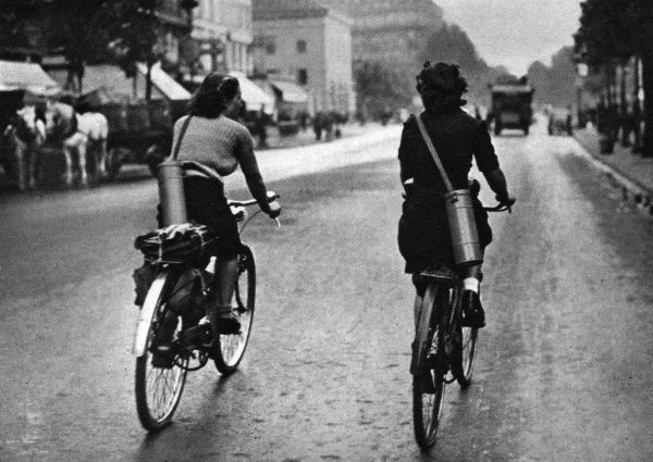 Two French women cycle to work in Paris with gas masks slung over their shoulders in canisters. Date: 1939