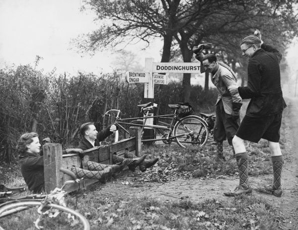 Four cyclists take a break from their ride and stop at a stocks for a bit of high- spirited fun; the two chaps pelting their companions seem to be rather enjoying it