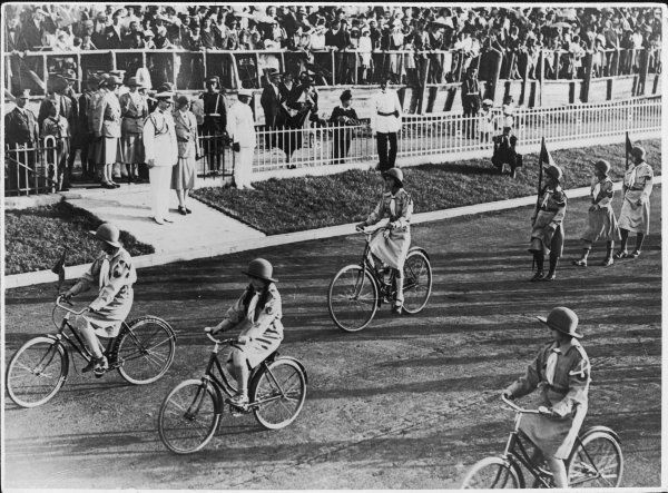 A parade of cycling Girl Guides pass King Carol and Princess Ileana of Romania