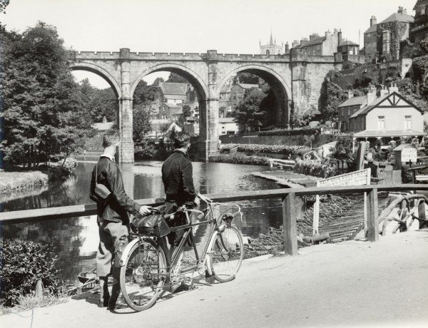 Two cyclists take a break on a bridge over the River Nidd at Knaresborough (in the West Ridings of Yorkshire) & admire the viaduct