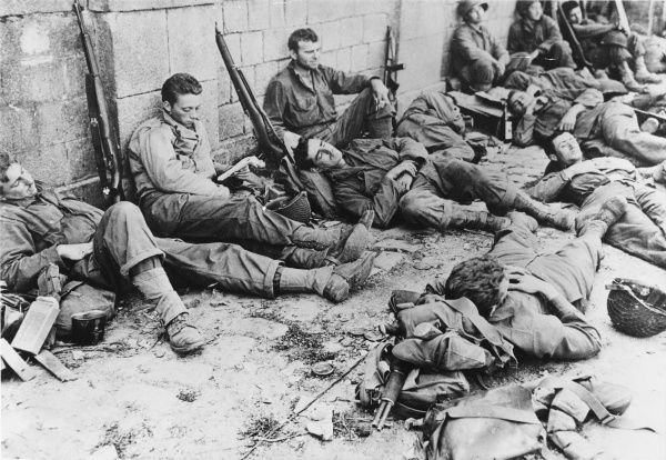 US troops rest after the initial assault on the Normandy coast