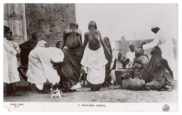 Two Sudanese women perform the DALLUKA dance, while someone shoos away the puzzled dog