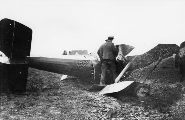 Men examine a damaged plane on an airfield during the First World War. Date: 1914-1918