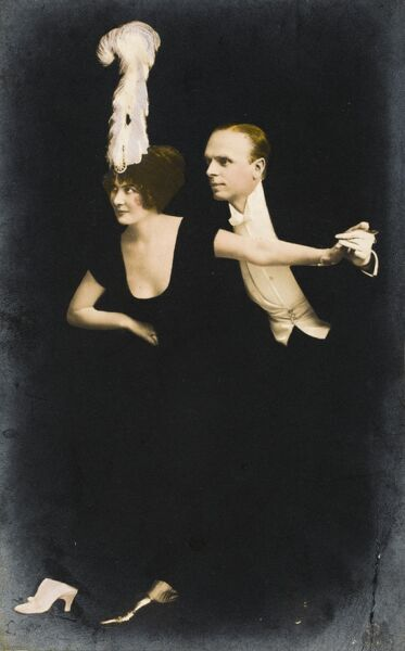 A twenties dancing couple - Madame is wearing a very fine white feather head adornment and Sir is dapper in white tie and very shiny shoes