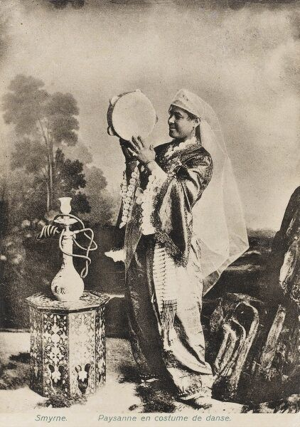 A Dancing Girl from Smyrna (Izmir) Turkey, holding a tamborine and standing before a small inlaid Mother-of-pearl octagonal table witha Hookah Pipe on top