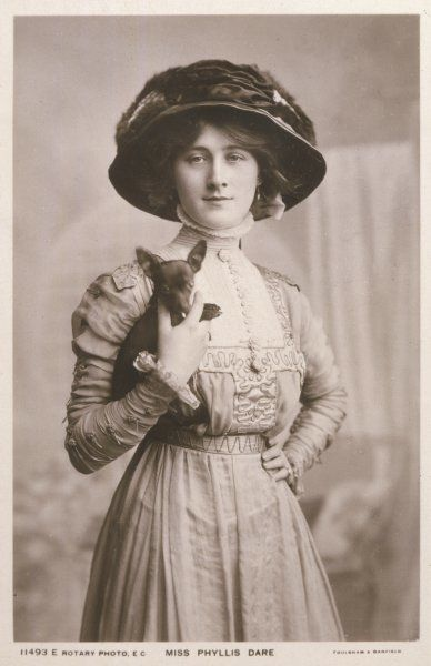 PHYLLIS DARE Actress, wearing a large hat and holding a small dog