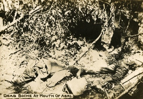 A dead German soldier, killed by American troops, near the entrance to a dugout on the western front during the First World War. Date: 1918