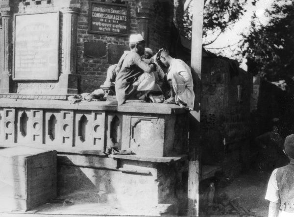 A barber cutting hair on a street corner, Delhi, India. Date: 1930s