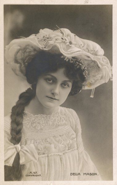 Delia Mason wears a hat composed of lace & gauze over a wire frame & trimmed with daisies. The brim is shaped into waves