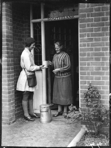 An old lady on the doorstep of her house ('Southbank'), pays the milk girl (wearing rather a short coat and long socks) for the pail of milk she has delivered, Margate, England