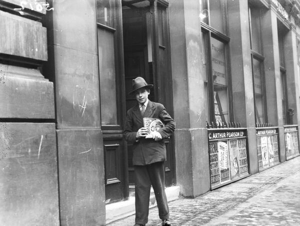 This smart young man, dressed in a suit and trilby, is apparently delivering copies of the women's magazine 'Woman's Own', which can be seen under his arm