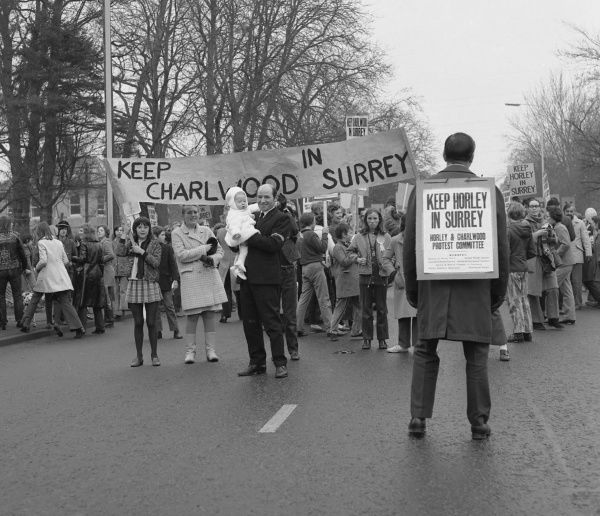 A group of people on a demonstration in the middle of a road, holding banners and placards, determined to keep Horley and Charlwood in Surrey. They must have been successful, because Horley and Charlwood are indeed still in Surrey!