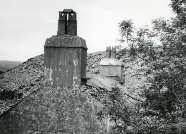 View of a derelict building in a slate quarrying area of North Wales. The roof of this house has several tiles (probably made of slate) missing