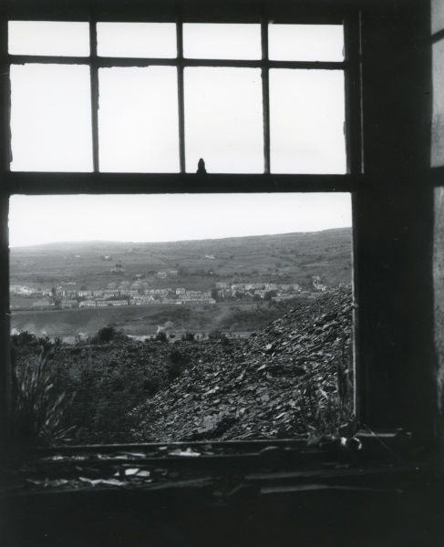 View through an open window of derelict slate workings in the Nantlle Valley, Caernarvonshire (now Gwynedd), North Wales. When an industry dies, the area dies too, and only the pollution is left