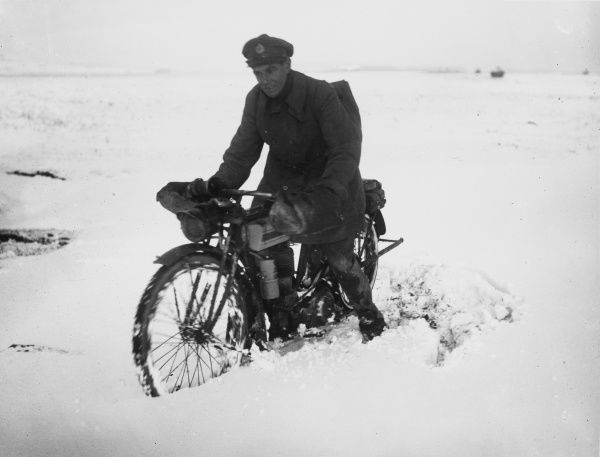 A motorcycle despatch rider in the snow at St. Pol in France on the British front during World War I in December 1917