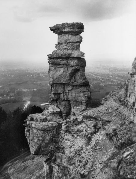 'The Devil's Chimney', a distintive natural rock formation on Leckhampton Hill, overlooking the road between Cheltenham and Birdlip, Gloucestershire, England. Date: late 1930s