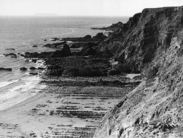 The rugged Devonshire coastline at low tide, near Hartland Quay, England. Date: 1930s
