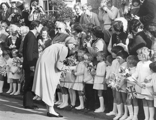 DIANA, PRINCESS OF WALES chatting to a line of little girls who, together with many other people, have come to see Diana and Charles at St Mary's, Isles of Scilly