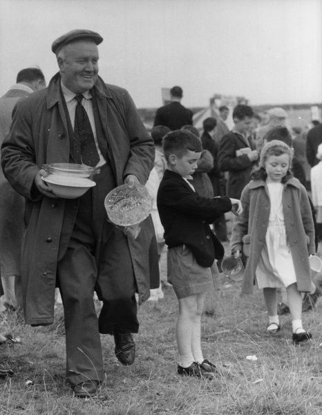 A happy middle-aged man and some children, with the glassware and ceramics they have won at the fair at Dingle racecourse County Kerry, Ireland. Date: 1962