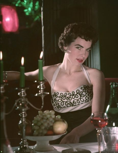 A sulty raven-haired woman in a halter-neck evening dress looks seductively into the eyes of her dinner guest opposite during a candle-lit meal for two