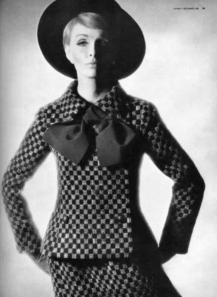 A smart suit in grey and black chequerboard wool by Marc Bohan for Christian Dior with a long, slim jacket, slightly basqued with a large bow at the collar, and a narrow matching skirt. Worn with a swaggering 'Franz Hals' hat in black felt