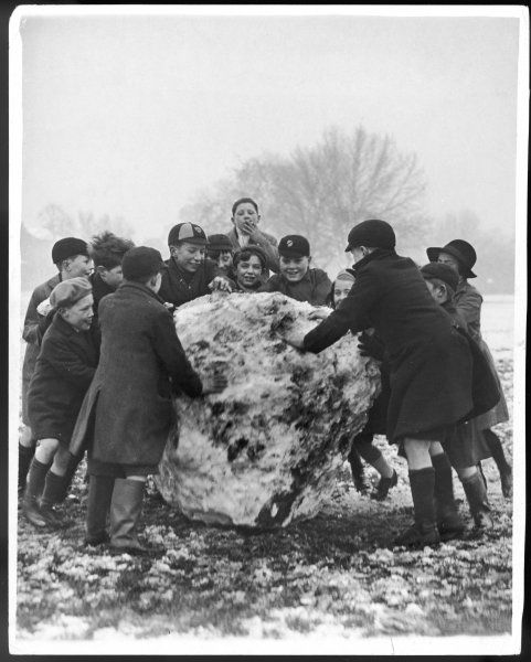 A group of schoolboys and girls in caps, hats and overcoats, rolling a dirty great snowball!