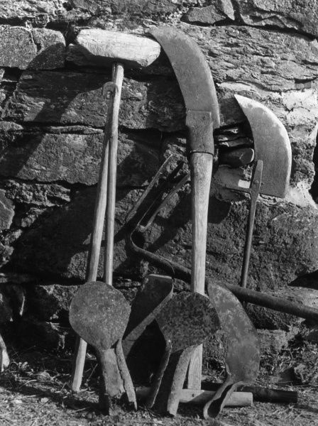 An impressive collection of ditching tools, leaning against a wall in Wales. Date: 1950s