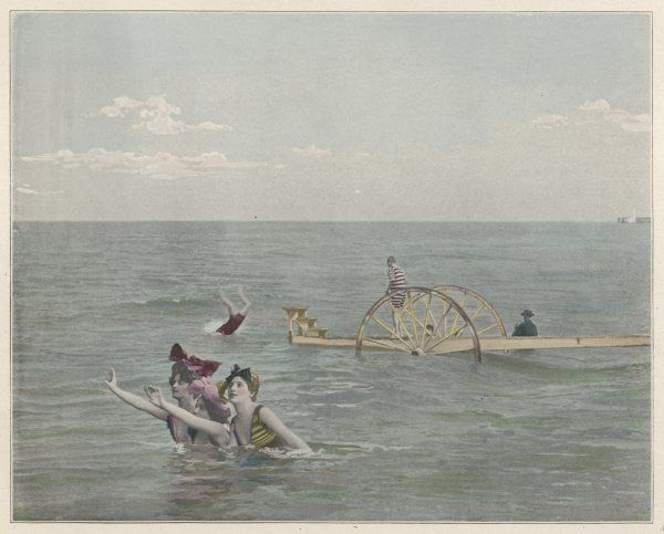 Swimmers make use of a diving platform on wheels, placed just off the shore