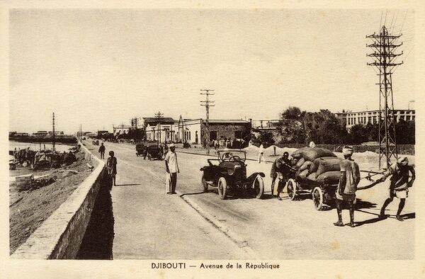 Djibouti, East Africa - Avenue de la Republique. It is nice to compare the difference between the colonial French mode of transportation and that being emplyed by the two Djiboutian grain merchants on the same stretch of road! Date: circa 1930s