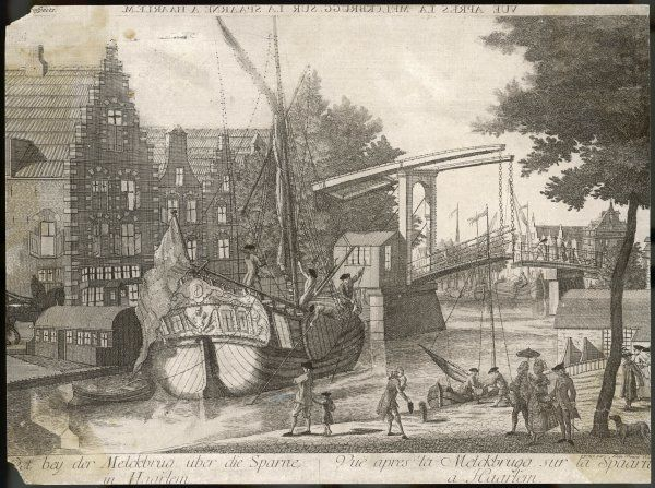 View of a busy dock scene on the River Spaarne at Haarlem. Sailors use poles to guide their ship through the Bascule bridge which is opening in the distance