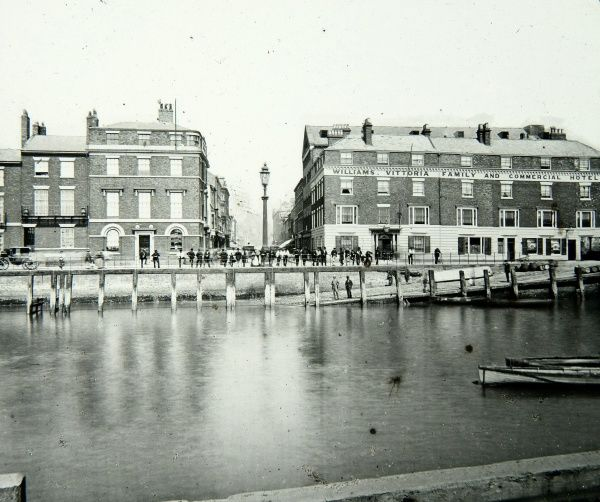 View of the dockside in Hull (Kingston upon Hull), Yorkshire, showing the Williams Vittoria Family and Commercial Hotel. A long line of people are leaning on the railings