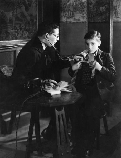 A general practitioner (Dr Meredith) listens with his stethoscope to a boy's chest in a rather unconventional looking surgery with tapestries on the walls