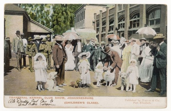 The Transvaal Kennel Club Show, Johannesburg, childrens class. In white dresses and hats, very young children hold their dogs for the judges inspection, watched by parents