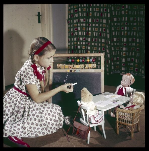 A smart little girl in a pretty dress with matching red shoes, ribbons and alice band, plays teacher with her blackboard and chalk. Her doll and teddy are the pupils