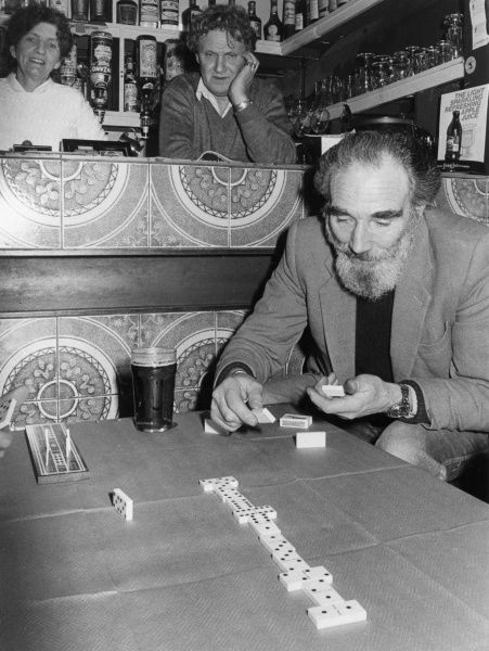 An elderly domno player enjoying a game at the Riviera Bar, Penzance, Cornwall