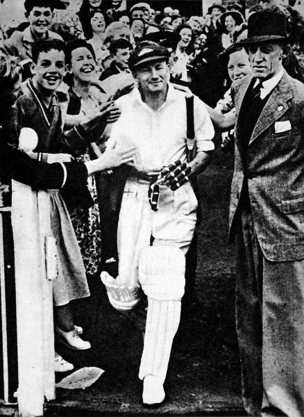 Photograph of Don Bradman going out to bat, during his last first-class cricket match; a game between Bradman's XI and L. Hassett's XI, held at the Melbourne Cricket Ground, December 1948. Bradman, characteristically, scored a century