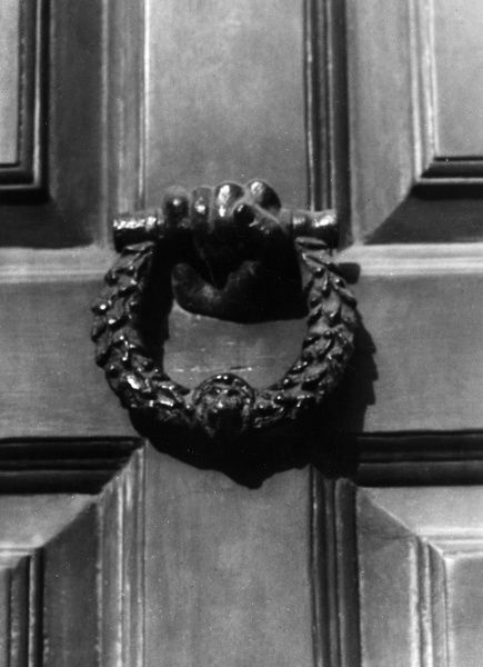 This fine door-knocker, in the form of a hand holding a circle of laurel leaves, with a lion motif, is on Dr Samuel Johnson's house at Gough Square, London. Date: 18th century